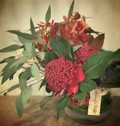 Small corporate fishbowl vase arrangement in reds - orchids and waratahs