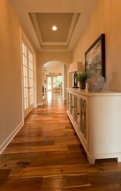 acacia hardwood flooring painted coffer ceiling with crown molding access to the kitchen and