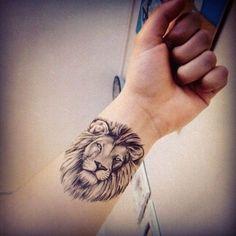 Joli tête de lion réaliste tatoué sur le poignet