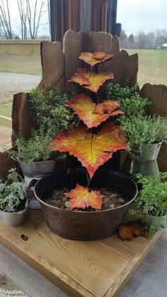 Water fountain made from cast concrete leaves and reclaimed wood surrounded by an herb garden.