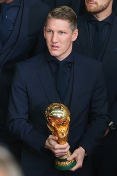 Bastian Schweinsteiger of German natioal football team poses with the FIFA World Cup Winners Trophy prior to the movie premiere 'Die Mannschaft' at Sony Center Berlin on November 10, 2014 in Berlin, Germany