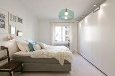 szare tapicerowane łóżko, krzesło vintage, nowoczesne zabudowane szafy i miętowa lampa w sypialni