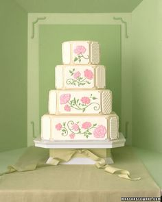 Smooth poppies and white-on-white patterns cover a square cake with cropped corners; gossamer ribbon brings out a hint of green in the fondant blanketing its tiers. The flowers were made using floodwork: A border was outlined and then filled in with royal icing, which has a fluid consistency. The blooms were transferred to fondant panels, which were then applied to the sides of the cake.
