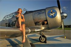 1940s pin-up girl sitting on the wing of a World War II T-6 Texan.