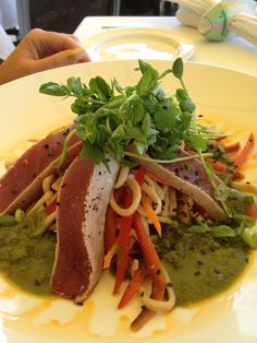 The seared rare ahi tuna salad, served on top of udon noodle, carrots and pea shoots with a ginger shallot vinaigrette