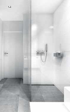 Contrast between big, grey tiles on floor, and shiny white tiles for shower walls.