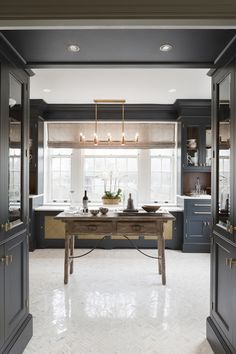 Matte charcoal gray cabinetry, brass hardware, marble countertop, crown molding/millwork. That slim herringbone marble floor is pretty fantastic too.