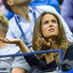 Andy Murray's wife, Kim Murray takes cover as it starts to pour with rain