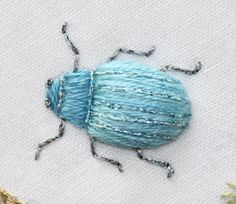 An embroidered bug- I love this. My guess is that this is padded satin stitch with straight stitch legs. Not sure what the glittery lines down the body are- couching perhaps?