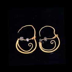 the slender style of these earrings are formed from rolled sheet gold which curves around, thickening towards the back where it splits to form a curved tail bel