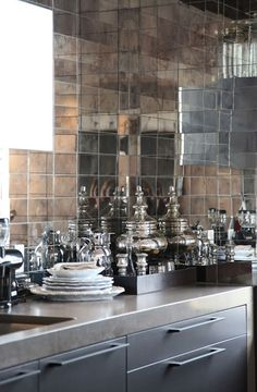 I kind of like the look of antique mirrored tiles behind the range (but way too much silver going on here)