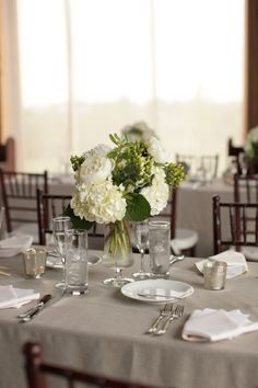 grey table cloth with white and green center pieces. this is really what we like. simple and clean looking.