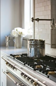 Kitchen Cabinets:Sherwin Williams Eider White SW 7014. Walls: Sherwin Williams Anew Gray / SW 7030.  The 38.5″ wide x 32″ tall iron piece behind the range is an antique Iron fire back dating to 1788 from France.  The brick on the ceiling are from General Shale. Color: Ironworks.  Backsplash: Tile: waterworks 3×6 color pumice / ARC36 Pencil Liner: Sonoma Tile Maker / Tantrum Blink / color Pewter. Grout: Custom Building Products #386 Oyster Gray.