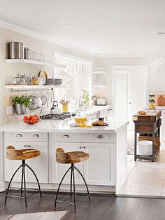 love these bar stools, the open shelving by the window, and the all white everything, of course...