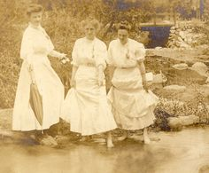 These three women are testing the water with their feet, while dressed in Edwardian fashion. Not the woman at left holding her parasol.