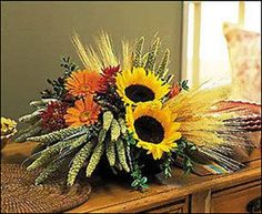 A Sunflower Harvest Sunflowers strike their pose, while wheat and millet wisp in the autumn wind. Fall harvest is truly captured in this remarkable arrangement. Chrysanthemums, gerberas and hypericum Sunflower Arrangements, Fall Floral Arrangements, Floral Centerpieces, Wedding Arrangements, Church Flowers, Funeral Flowers, Fall Flowers, Thanksgiving Flowers, Halloween Flowers