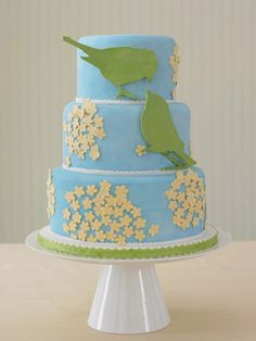 A Modern Blue Bird Wedding Cake    Two green love birds pop off this hand-painted blue wedding cake. Small yellow sugar flowers finish it off.    (From Lovin Sullivan Cakes, New York, NY)