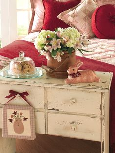 Dress up a dresser or other small table for Easter with some decorative eggs under a glass dome, a firkin full of spring blooms and a cute bunny figure.