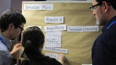 Der Veranstaltungsplan für die einzelnen Sessions wird am jeweiligen Barcamp-Tag morgens durch die Teilnehmer festgelegt. Jeder kann sich einen Vortrag oder mehrere Themenvorschläge überlegen. Hier seht Ihr, wie Daniel Amersdorffer, Annkathrin Wagner und Daniel Sukowski die Themenvorschläge auf dem Sessionplan koordinieren.