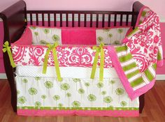 Suzann Baby Bedding  Included in this modern 3 piece crib set is the bumper, soft minky backed blanket, and tailored border detail crib skirt.  There is lots of detail in this custom set including soft hot pink minky, green apple grosgrain ties, coordinating dots, floral, stripe, and mod dandelion cotton prints in lime, white, and hot pink.