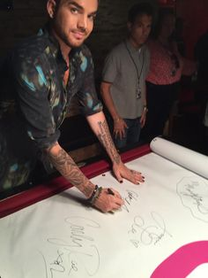 @AdamLambert signing the @HITS973 Wall Of Fame! #GhostTown #HITSSessions #Glamberts
