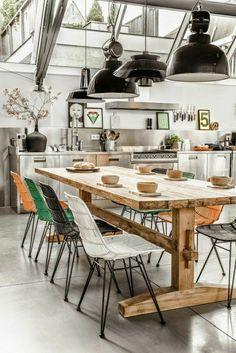 une cuisine avec une table haute en bois, chaises de cuisine, plafond en verre, sous pente