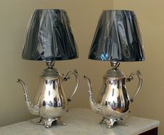 Matching set of vintage silver plated teapots converted into lamps. Shown with custom designed black fabric shades.