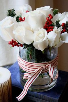 Clear vase with Christmas greenery inside, with an arrangement of stunning and crisp white roses paired with red berries