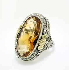 Antique Imperial Topaz and pearl ring. This piece is set with a stunning Imperial Topaz oval shape stone encased with a string of the tiniest, delicate pearls. It is bound by yellow gold flowers and a very intricate filigree setting. A one-of-a-kind piece. Imperial Topaz, with its distinct hues, is the rarest topaz variety.