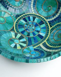 Mosaic dish made of hand cutted stained glass pieces, glass tiles and glazed ceramic tiles on bamboo dish. Turquoise grout. Dimensions: diameter: ~ 36cm/~14 height : 10 cm / ~4