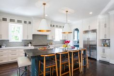 Floor-to-ceiling cabinets provide much-needed storage, while the blue island adds a punch of color and the perfect spot for eating and doing homework. The entire space is designed to be family friendly, but still embraces luxurious materials, like granite countertops and mirrored tile backsplash.