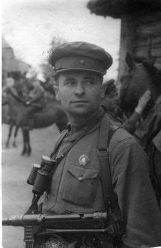 """Partisan commander Alexeii Pakhomov, 3rd Partisan Brigade, Leningrad region poses for the camera with his """"requisitioned"""" German MP-40 SMG and the standard issue German army Zeiss field glasses. Pinned to his chest is the Order of Lenin. Partisan units were often commanded by regular Red Army officers."""