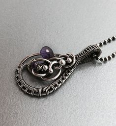 Amethyst necklace, Amethyst pendant, Purple gemstone pendant, Wire wrapped amethyst pendant, Silver amethyst pendant.  A beautiful asymmetrical wire wrapped pendant made with sterling and fine silver. This pendant is adorned with a sparkling faceted briol