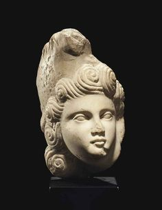 A ROMAN MARBLE HEAD OF A YOUTH CIRCA LATE 1ST-EARLY 2ND CENTURY A.D. Perhaps Orpheus, from a relief or a sculptural group, depicted nearly in the round, his head turned to his left, wearing a Phrygian cap, with bird claws gripping the hooked top, his luscious snail curls framing his face 7 5/8 in. (19.4 cm.) high