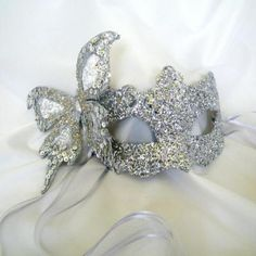This handmade papier mache base is an authentic Venetian Mask and has particularly wide eye holes which are incredibly flattering and comfortable. Punched all over in a delicate filigree design then triple dipped in silver shimmer, subtle but catches the light at an evening event perfectly..Then the perfect decorated silver butterfly rests on the side, too gorgeous!  Fastens with silver organza ribbons