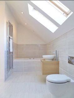 window on angled ceiling.  Neutral beige bathroom, fully tiled around bath:
