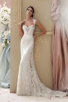 David Tutera for Mon Cheri - Lourdes. Corded lace appliqué and tulle over soft satin slim A-line cage wedding dress with lace cap sleeves, tulle and corded lace appliquéd deep Queen Anne neckline, sweetheart bodice adorned with hand-beaded jeweled motif and corded lace, scalloped lace open keyhole back bodice with double covered buttons, soft satin slim underskirt with sweep train, tulle and matching lace appliquéd cage overskirt with scalloped hem features eyelash trim and chapel length ...