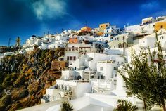 White-washed houses and blue domes on cliff top. Santorini Photo Safari find more → http://www.santoriniphotosafari.com/