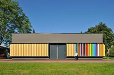 A building with wooden shutters along the whole side, uncolored on one side and brightly colored on the other.  Kindergarten Kekec, Arhitektura Jure Kotnik, Ljubljana Slovenia, 2011, from Arcady of Playscapes.