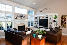 Great room with a gas fireplace and a wall of windows. The room also has built-in custom shelves.