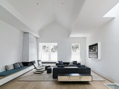Fronting Alamo Square Park, the living room's pitched ceiling creates an expansive space for socializing and relaxing. The space is accented by a custom sofa and window seat by Franciscan Interiors, rocking chairs from B&B Italia, a Lake low credenza by BDDW. The fireplace-adjacent bench seating is upholstered in William Yeoward Alverdia fabric in Ocean, complementing the teal accents in the adjoining dining room and kitchen.