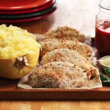 """Chicken Parmigiana with Spaghetti Squash - The trick to a crisp but healthy Parmigiana is """"bake-frying."""" Canola oil is ideal to bake-fry breaded chicken in a very hot oven because of its high heat tolerance (smoke point 468°F/242°C). Using spaghetti squash instead of angel hair pasta provides four times fewer calories per cup (174 versus 42 calories).  Recipe by Dawn Jackson Blatner, R.D., C.S.S.D., L.D.N."""