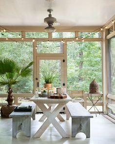 """We eat every meal out here,"" say the owners of the screened-in side porch in this rustic South Carolina getaway. They found the bee skep in an Atlanta garden store. - HouseBeautiful.com"
