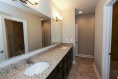 A large and functional jack and jill bathroom located in the lower level of this patio home! With double sinks, loads of storage, and a private shower and toilet space makes this bathroom easily functional.