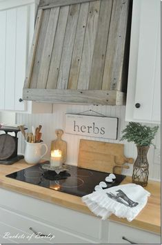 Cover a kitchen vent in reclaimed wood to give the room a rustic vibe.