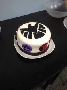 Gina Bigler's SHIELD cake, with other superhero symbols surrounding it (Black Widow's red hourglass, Hawkeye's purple crosshairs, Thor's hammer, green Gamma symbol for Hulk, Captain America's star shield, and Iron Man's chest device.)