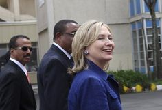Secretary of State Hillary Clinton is escorted as she arrives at the Bole International Airport in Ethiopia's capital Addis Ababa