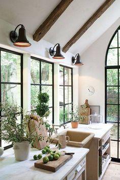 white marble countertops, wood beams, black windows