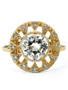 Sienna is a brilliant example of artistry, balance, and vision. Her stunning diamond center stone is wrapped in a handmade bezel, adorned with the most delicate gold beading. Dana & Rad further designed a deco-inspired halo around the bezel, creating a unique display of geometric form & antique whimsy. #UniqueEngagementRing #YellowGold #DanaWaldenBridal