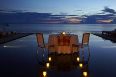 Romantic dinners, held ocean side at Viceroy Maldives, illuminated with candles at sunset.